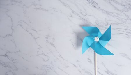 Wind wheel paper real toy on white color marble stone background which made from origami hand made on light blue colour japanese special material and wood stick