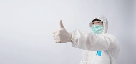 Wide angle images of Asian woman doctor in PPE suit or personal protection equipment and medical goggles, mask, gloves and showing thumb up or like it symbolic which represent happy moment with low pandemic 版權商用圖片