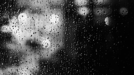 Window and rain drop in condominium or apartment room on a rainy day in Bangkok Thailand and background outside is blurred bokeh of raining city light and natural tree and sky. 版權商用圖片 - 149478100