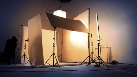 Shooting studio for photographer and creative art director with production crew team setting up lighting flash and LED headlight on tripod and professional equipment for portrait model photo shoot and video online filming