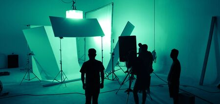 Shooting studio for photographer and creative art director with production crew team setting up lighting flash and LED headlight on tripod and professional equipment for portrait model photo shoot and video online filming 版權商用圖片 - 147934379