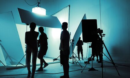 Shooting studio for photographer and creative art director with production crew team setting up lighting flash and LED headlight on tripod and professional equipment for portrait model photo shoot and video online filming 版權商用圖片 - 147934428
