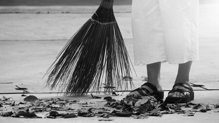 Woman sweeping dry leaves on the cement floor with long wood broom and keeping outdoor clean everyday which images showed middle aged female leg with white pants and black color sandal.