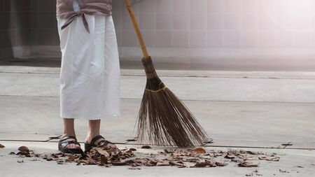 Woman sweeping dry leaves on the cement floor with long wood broom and keeping outdoor clean everyday which images showed middle aged female leg with white pants and black color sandal. 版權商用圖片 - 149328121
