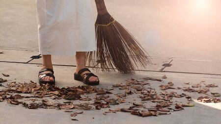 Woman sweeping dry leaves on the cement floor with long wood broom and keeping outdoor clean everyday which images showed middle aged female leg with white pants and black color sandal. 版權商用圖片 - 149329502