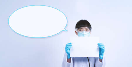Asian woman doctor holding a blank paper in hand and copy space and she wear medical glove and face mask and doctor suit for protect virus pandemic. studio shot on plain background. Stok Fotoğraf