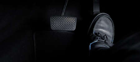 Man foot and accelerator and brake pedal inside the car or vehicle and copy space which black color leather shoe stepped on it for speed up or control automobile pace power.