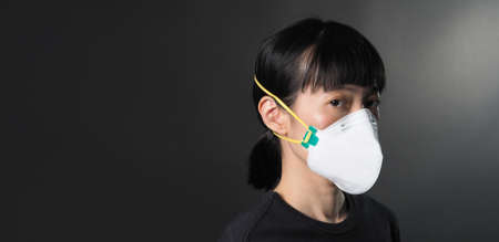 Middle aged of asia chinese woman wearing medical N95 mask that help prevent or protect her from coronavirus or covid-19 pandemic and safety from air pollution. and copy space Standard-Bild