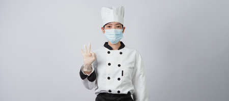 Asian woman chef in white color uniform with hygienic such as medical face mask and rubber hand glove for prevent or protect covid-19 or coronavirus pandemic. Studio shot and copy space.
