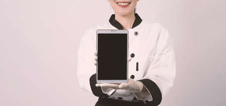 Middle aged of asian woman chef holding smartphone or digital tablet and received order from online shop or merchant application. she smiling in chef uniform and standing in studio with white color background.