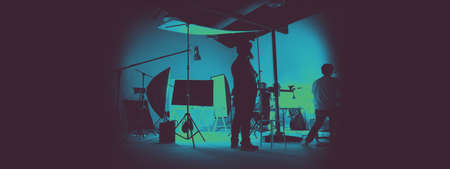 Two tone images of behind the scene of photo shooting production set up in the big studio. Professional crew team working and camera equipment in silhouette. And copy space added.
