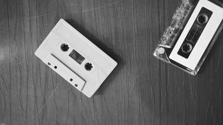 Close-up images of cassette tape on retro wood table. represent nostalgia mood or moment to 80s or 90s that most of audio music or songs recorded in compact and handy device technology.