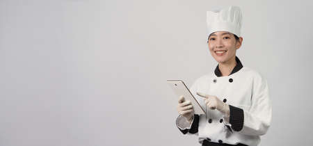 Asian woman chef holding smartphone or digital tablet and received food order from online shop or merchant application. she smiling in chef uniform and standing in studio with white color background.