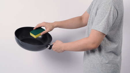 Asian man in grey color T shirt cleaning the non stick pan with handy dishwashing sponge which yellow color on the soft side and green on hard side for hygiene after cook and white background studio shot Stock Photo