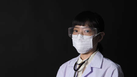 Doctor Wearing Medical Mask and clear goggles or glasses and stethoscope on the neck and white uniform. 免版税图像