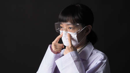 Doctor Wearing Medical Mask and clear goggles or glasses and stethoscope on the neck and white uniform. Asian female doctor or scientist in protective facial masks on black background.