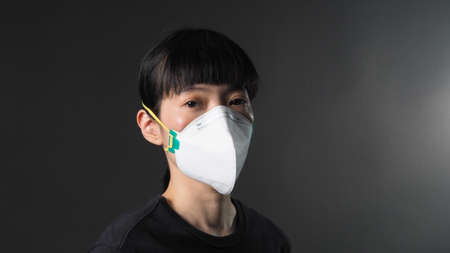 Asian girl in a mask on a black background in Quarantine situation. 免版税图像