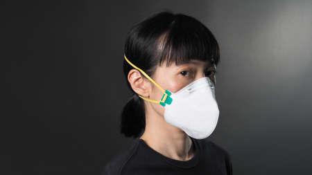 Asian girl in a mask on a black background