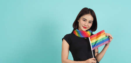 Portrait of young girl holding an LGBT flag standing against a blue green background studio. Asian LGBTQ woman with rainbow scarf on neck. look smart bright and energetic cheerful. LGBTQ concept. Foto de archivo