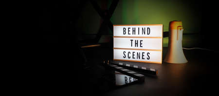 Behind the scenes letterboard text on Lightbox or Cinema Light box. Movie clapperboard megaphone and director chair beside. Background LED color change. static camera in video production studio.
