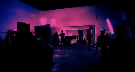Behind the scenes of shooting video production and lighting set for filming movie which film crew team working in silhouette and professional equipment in studio for video. video production concept. 版權商用圖片