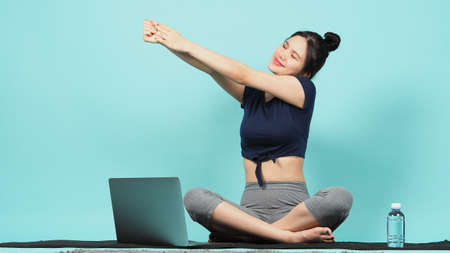 Fitness influencer. Sporty woman workout training online via laptop. copy space. blue green background. Athletic woman blogger in sportswear shoots video on notebook camera as exercises at home. Exercise online training.