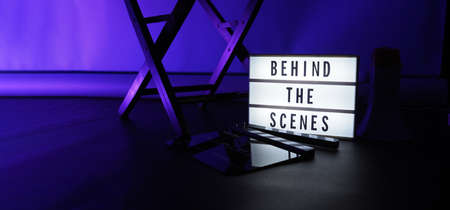 Behind the scenes light box. Text on cinema light box. Megaphone and director chair and movie slate beside. Background LED color. Camera in video production studio. Behind the scene concept.