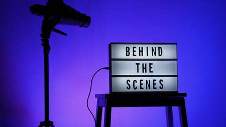 Behind the scenes letterboard text on Lightbox or Cinema Light box. Multi color LED on background. Sillhouette flash snoot hood on tripod. video production studio. Behind the scene Lightbox
