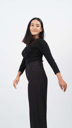 Young woman posing in black shirt and pants in the studio on white background. Sexy Asian black hair girl with full lips pose to camera. Attractive female with big breast. posing in studio shooting.