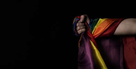 Flag of pride. LGBTQ flag and hand. Lesbian Gay Bi sexsual Transgender Queer or homosexsual pride Rainbow flag. black background. Represent hand symbol of freedom equality.
