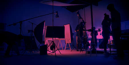 Neon Blue pink color shooting. behind the scene of video production set up in the big studio. Crew team working and camera equipment in silhouette. Movie production industry. Lighting set up.