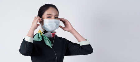 Cabin crew or air hostess with face mask in   pandemic.   New normal lifestyle in airline business. Pretty stewardess woman. 免版税图像