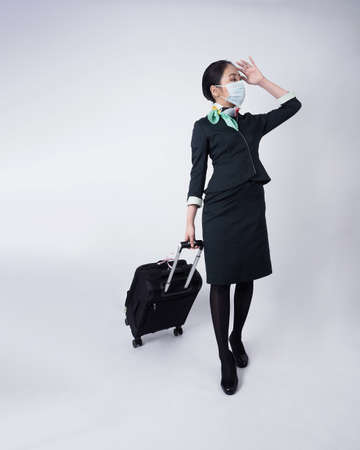 Cabin crew or air hostess with face mask in Covid 19 pandemic. Flight attendant wear medical mask to prevent coronavirus infection. New normal lifestyle in airline business. Pretty stewardess woman. 免版税图像