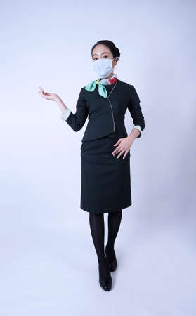 Cabin crew or air hostess with face mask in   pandemic .  New normal lifestyle in airline business. Pretty stewardess woman. 免版税图像