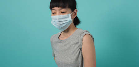 Vaccine Concept. Woman waiting for coronavirus vaccine injection by doctor. Asian woman with medical mask open shoulder and upper arm on blue green background. Waiting for vaccination.