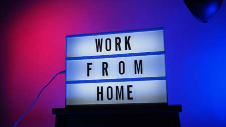 Work from home light box in studio. WFH Text on lightbox. Represent work from home for social distancing concept during coronavirus pandemic. WFH message on light board COVID 19 quarantine situation. 免版税图像