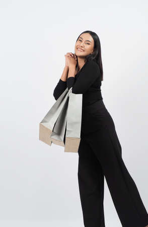 Love Shopping concept. Beautiful Asian woman carrying gray color bags shopping online. isolated on white studio background. online shopping bag. black hair woman love shopping online. Online purchase