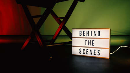 Behind the scenes letterboard text on Lightbox or Cinema Light box. Movie clapperboard megaphone and director chair beside. Background LED color change loop. static camera in video production studio. 免版税图像