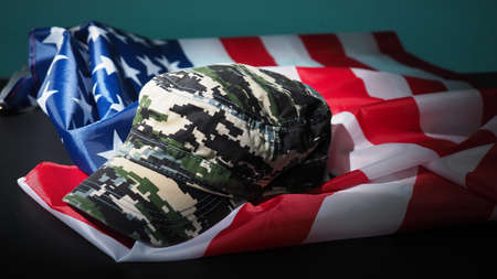 Military hat or bag laying with american flag. Soldier hat or helmet with national american flag on black background. Represent military concept by camouflage object and USA nation flag. 免版税图像