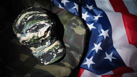 American flag and Military hat or bag. Top view angle. Soldier hat or helmet with national american flag on black background. Represent military concept by camouflage object and USA nation flag.