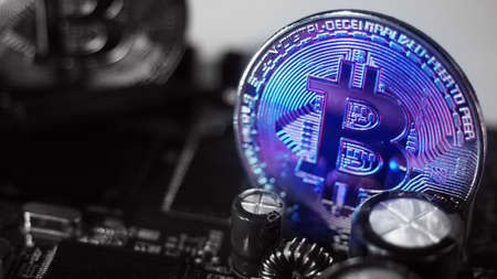 Bitcoin and semiconductor. Represent mining in Cryptocurrency cause global warming. Bitcoins on CPU board. Close-up Bitcoin with blue and pink light. circuit board with coin. Online asset concept. 免版税图像