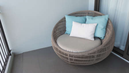 Outdoor beach chair on the hotel room balcony or terrace which made from natural wood called rattan and brown color round shape and look luxury for relaxing or sleeping or for party.