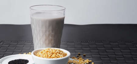 Soy milk blended with black sesame in clear glass on black plate mat. Black sesame seed and soy beans in a cup. Black sesame soy bean blended milk. Healthy drink with natural ingrediant. Soya milk.