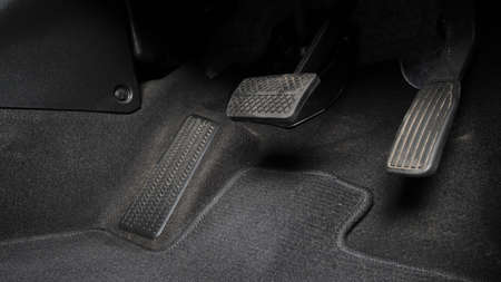 Man foot and accelerator and brake pedal inside the car or vehicle and copy space which black color leather shoe stepped on it for speed up or control automobile pace power. Automobile Driving concept.