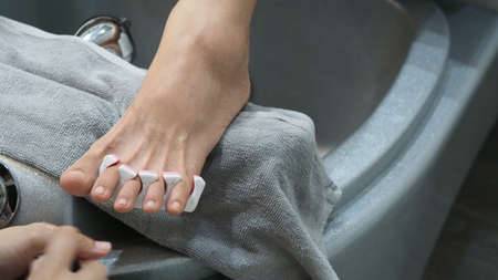 Foot Spa. Woman bare feet massaging in soap water machine at spa shop. Feet of women entering the footbath in the hot water handheld.feet massage with oil in resort spa salon. relaxation skin care.