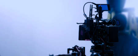 Video production behind the scenes. Making of TV commercial movie that film crew team lightman and cameraman working together with film director in studio. film production concept. Silhouette style. 免版税图像