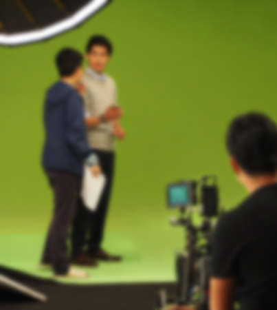 Blurry images of making TV commercial movie video in big green screen background. Film crew team working with actor. Recording by professional digital camera and lighting set. film behind the scenes 免版税图像