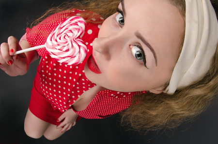 fish eye: Beautiful young pin-up woman wearing red cloths with radiant red lipstick. Dark background. Fish eye shot.