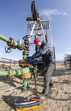 Worker reparing wellhead with the wrench in the oilfield. Tool box foreground, pumpjack background. Oil and gas concept. Fish eye shot.