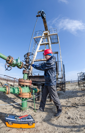 Worker reparing wellhead with the wrench in the oilfield. Tool box foreground, pumpjack background. Oil and gas concept. Fish eye shot. Stock Photo